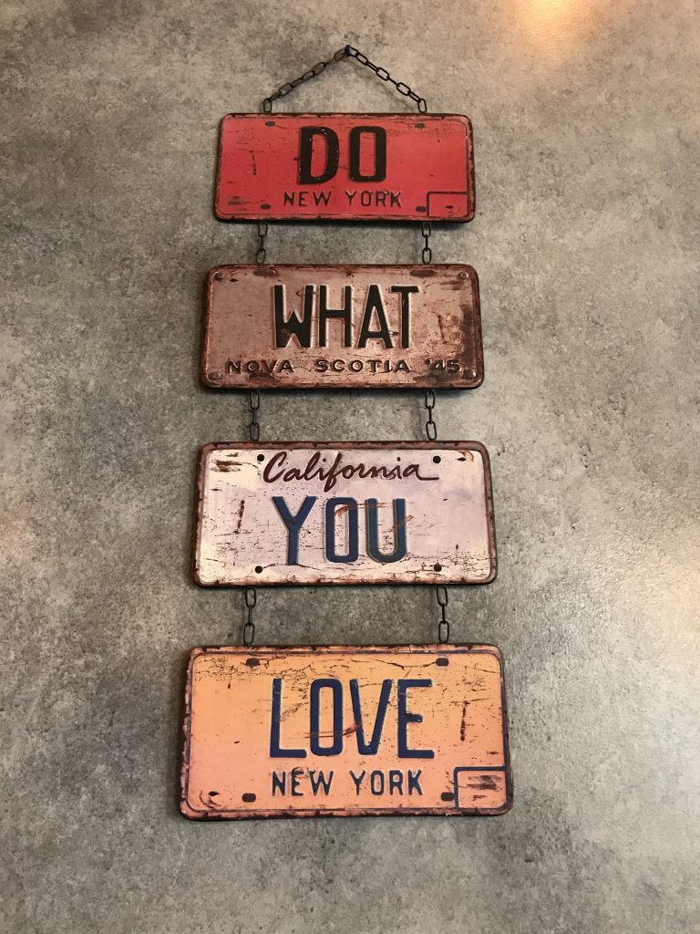 Looking at a sign hanging on a wall made of various sizes and colors which spells Do What You Love